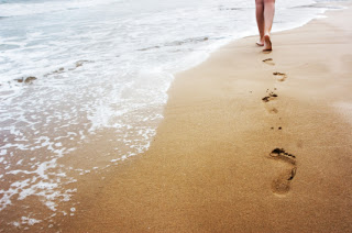 A young woman walking on the sand.