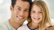 Man and young girl in living room smiling